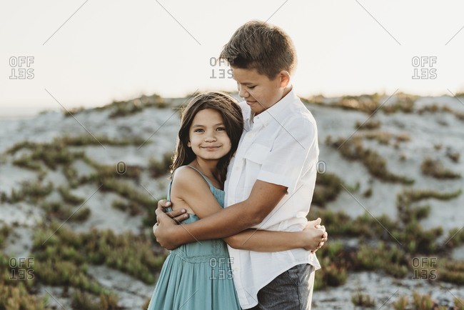 Preteen boy in white shirt hugging his younger sister at the beach