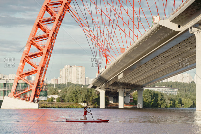 Side view of woman standing on paddle board in river and rowing with paddle under bridge in city