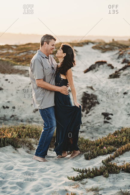 Loving embrace between barefoot mid-40's couple standing in sand