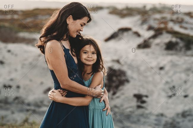 Beautiful 45 yr old mom embracing young daughter at the beach