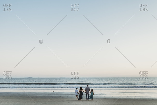 Young family standing on beach holding hands looking out at the ocean