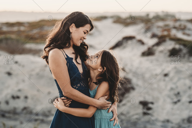 Happy mother hugging 8 yr old daughter at the beach