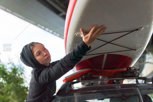 Low angle of female surfer putting paddle board on roof of automobile after training