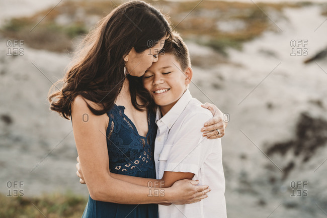 Loving mother embraces smiling preteen son