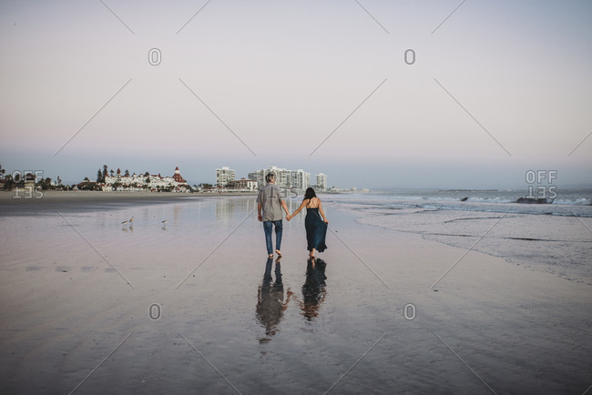 Mid-40's couple holding hands and walking barefoot along the beach
