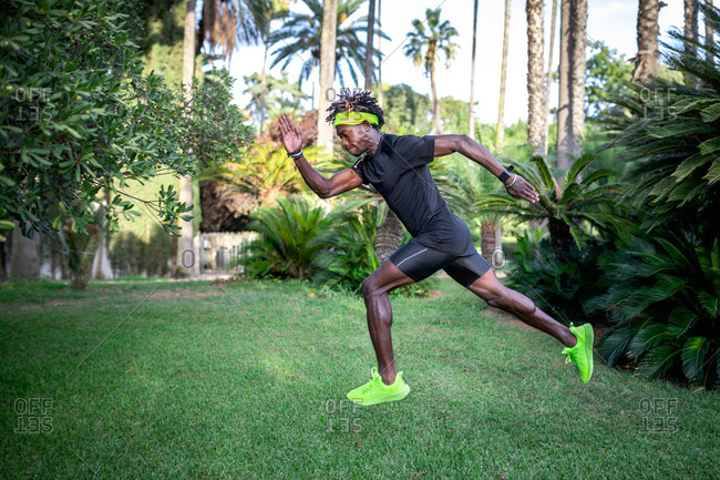 Side view of determined young African American male athlete in stylish sportswear running on green lawn in park