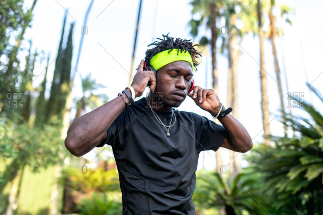 Young African American male athlete in sportswear listening to music with his headphones keeping hands on the headphones and closed eyes while standing in green tropical park