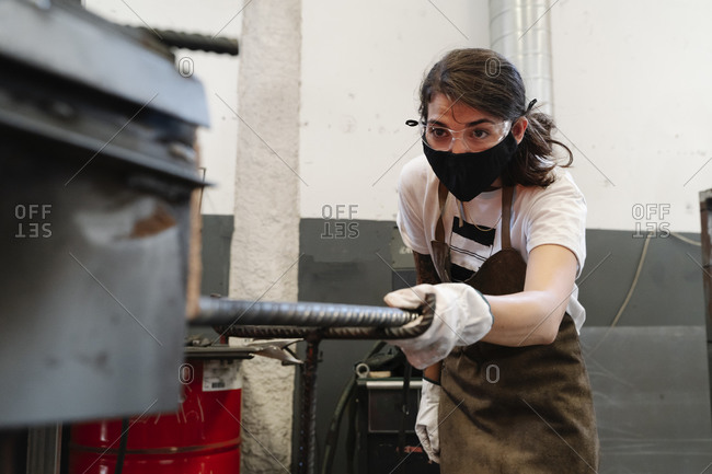 Female blacksmith in protective mask in workshop doing metal work