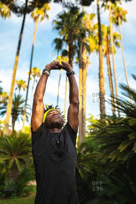 Confident young African American male athlete in trendy sportswear stretching arms while training in park with green tropical trees