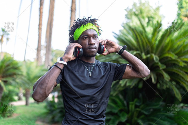 Young African American male athlete in sportswear listening to music with his headphones keeping hands on the headphones and looking away while standing in green tropical park