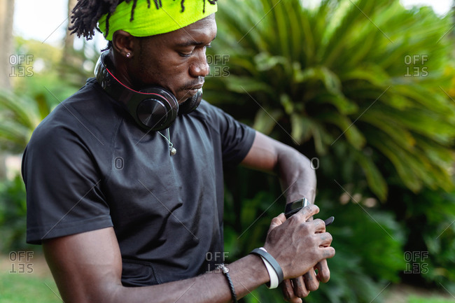 Stylish young African American male runner with headphones on neck checking sport results on fitness tracker during training in green tropical park