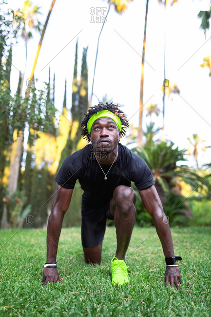 Determined young African American male athlete in stylish sportswear standing in low start position on green lawn while preparing for running in park