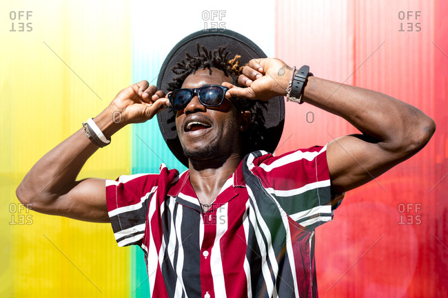 Young African American male in striped shirt and trendy sunglasses and hat looking at camera while standing against multicolored wall