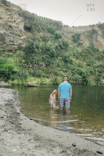 Father and daughter playing in the water at a scenic river spot