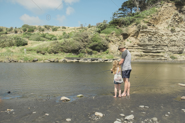 Father and daughter fishing at a scenic river spot