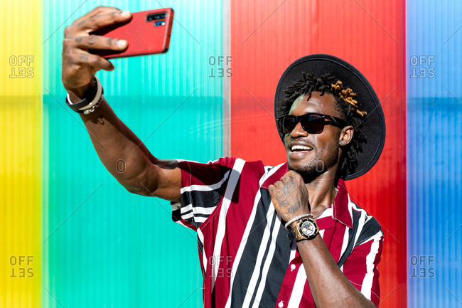 Optimistic young tattooed African American male in bright striped shirt and hat with trendy sunglasses and wristwatch taking selfie on mobile phone while standing against colorful wall