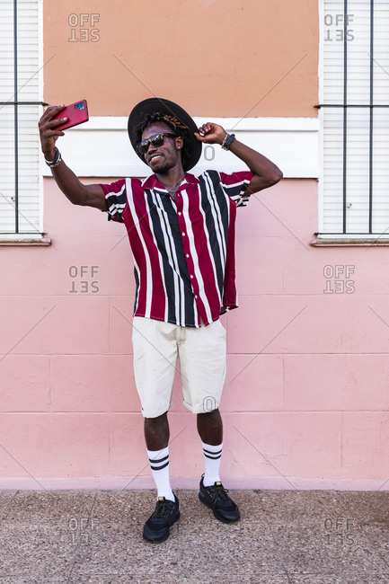 Funky young African American guy in stylish outfit and accessories standing near colorful wall and taking selfie on smartphone on urban street
