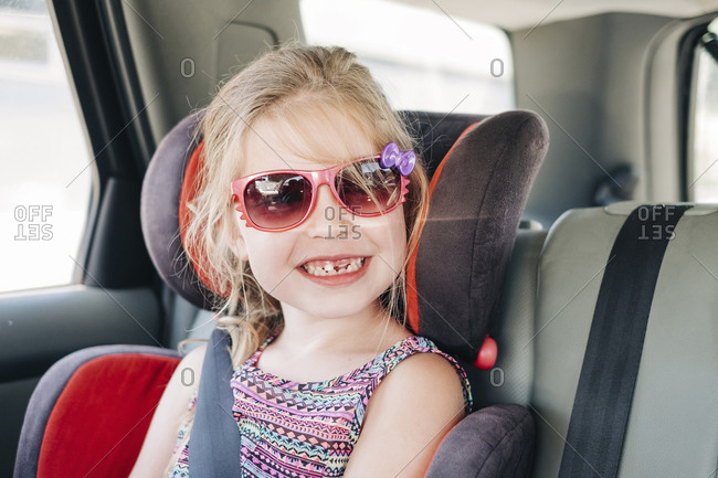 Young girl wearing sunglasses sitting in a car seat