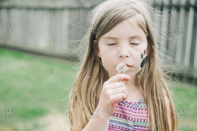 Young girl blowing a dandelion in the backyard