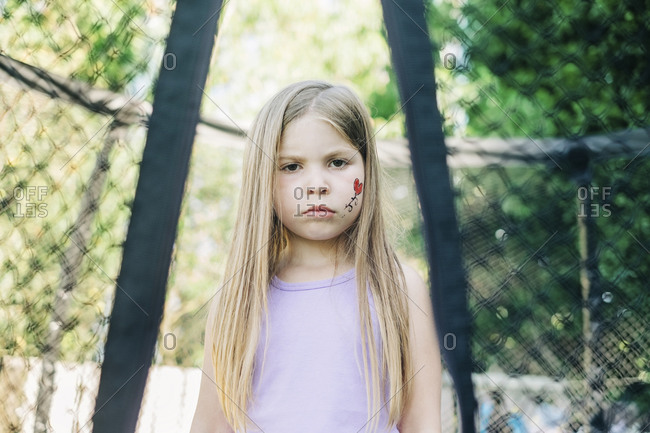 Unhappy young girl standing on a trampoline between the netting