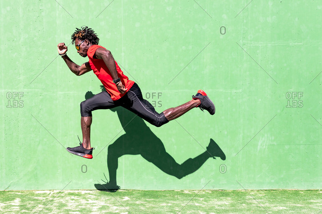 Side view of black sportsman in activewear in moment of jumping during intense workout on sunny day