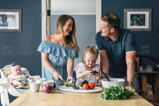 Family with young children laughing while making healthy food