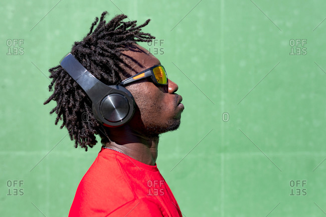 Side view of serious African American male athlete listening to music in headphones while preparing for training in summer