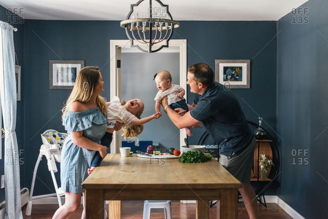 Parents holding daughters over the table as they laugh and play