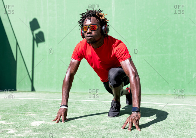 Determined black sportsman with dreadlocks stretching body while warming up before training and listening to music in headphones
