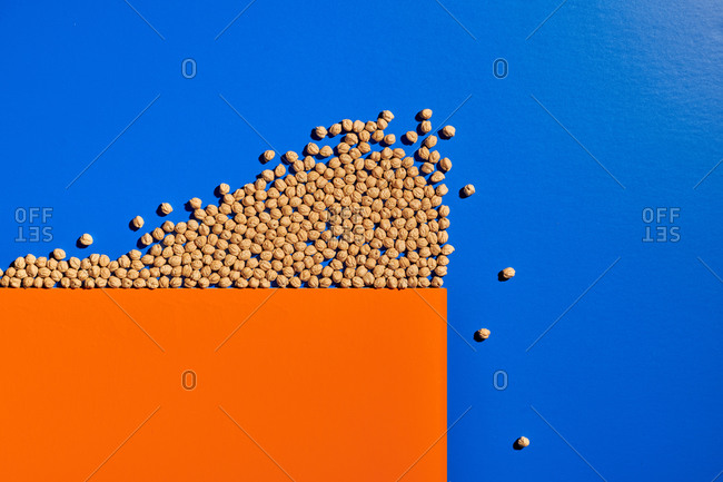 Top view of grain representing crowd of people falling from edge of cliff made of orange paper and demonstrating concept of herd instinct of human beings