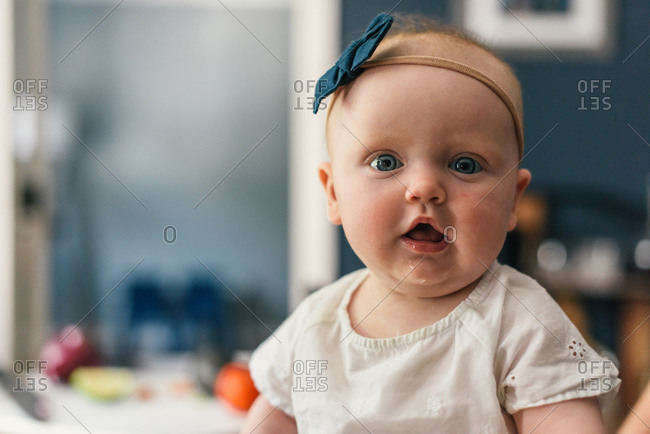 Young baby girl looks at the camera with drool and on food table