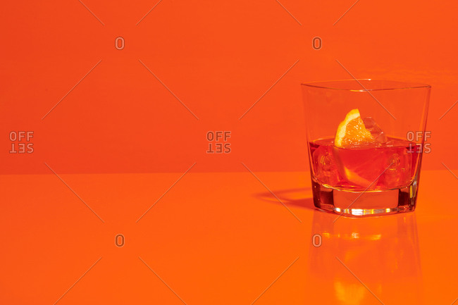 Crystal glass of alcohol drink with slice of lemon and ice cubes placed on table in studio on orange background
