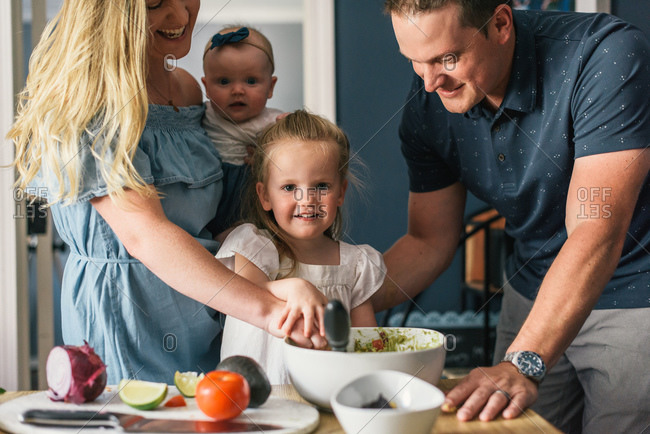 Daughter looking at camera as family makes bowl of guacamole together