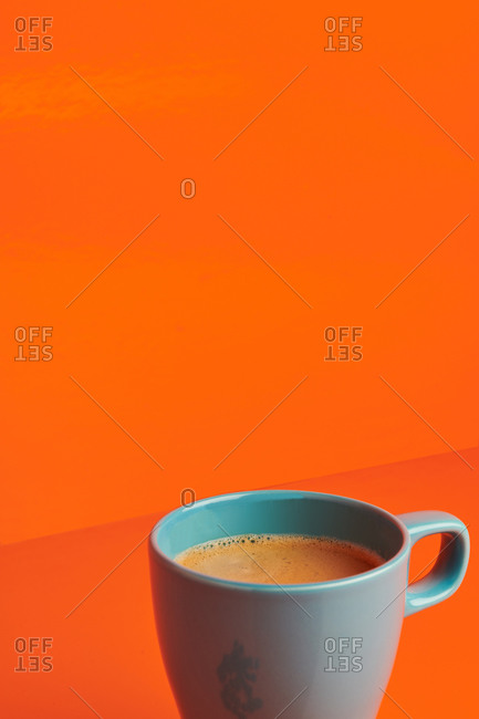 Gray ceramic mug filled with brown colored beverage placed on bright orange background