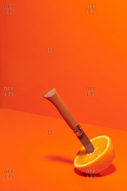 Half of ripe juicy orange with sharp knife placed on orange background in studio
