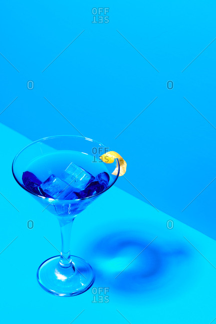 Crystal goblet with alcohol beverage and slice of lemon placed on blue background in studio
