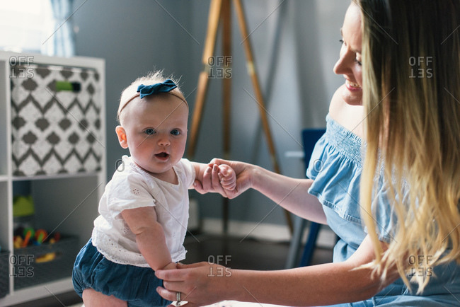 Mother and baby daughter playing together in family living room
