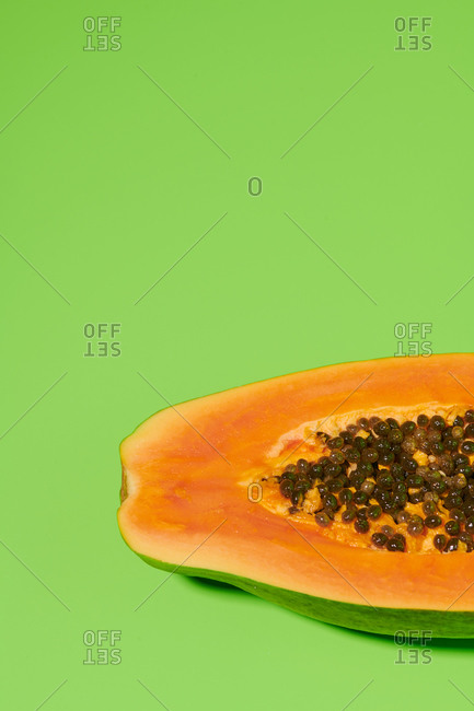 From above closeup of fresh ripe halved papaya with seeds placed on bright green background