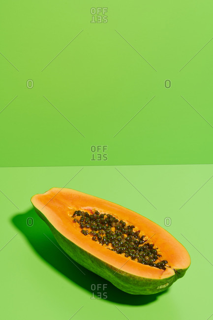 From above fresh ripe halved papaya with seeds placed on bright green background