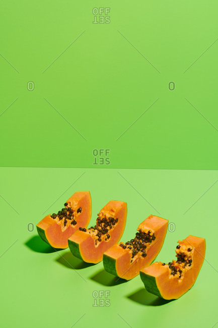 From above of cut pieces of fresh ripe sweet papaya fruit arranged in row on bright green background