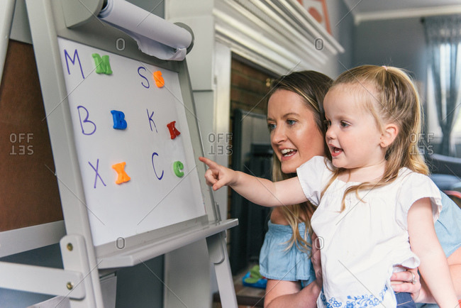 Daughter pointing to alphabet board as they learn together at home
