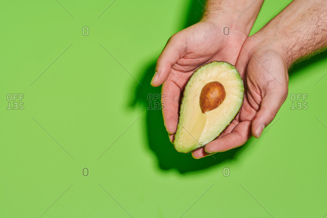 From above of crop unrecognizable person holding halves of fresh ripe green avocado with seed against bright green background