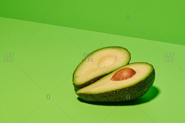 Fresh green natural avocado cut in half with seed placed on bright green background