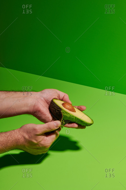 Crop unrecognizable person removing peel from fresh ripe avocado against bright green background