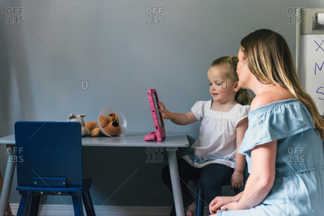 Daughter showing mother games on tablet while they play and learn