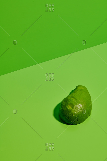 Fresh green natural avocado on bright green background