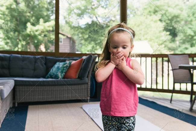 Young girl holding face in outside porch in fitness clothes