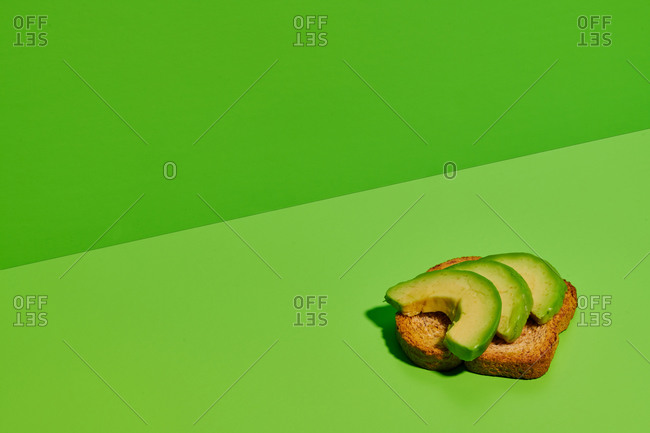 Delicious healthy bread toast with fresh sliced avocado placed on bright green background