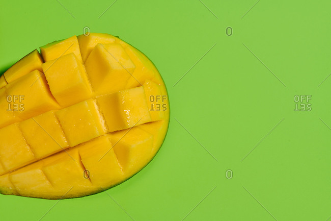 From above closeup of fresh ripe juicy mango half sliced into pieces on bright green background