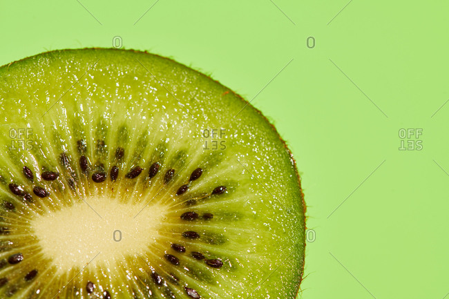Half of delicious ripe kiwi fruit placed on green background in modern studio